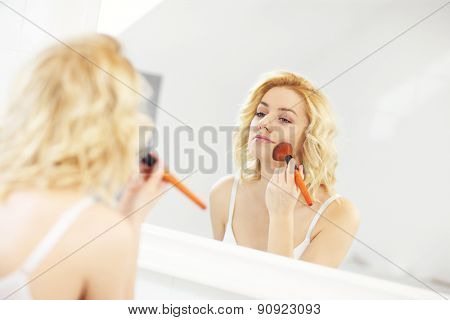 A picture of a young woman applying face powder in the bathroom