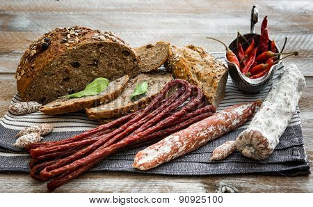 bread with dried sausages on a wooden table