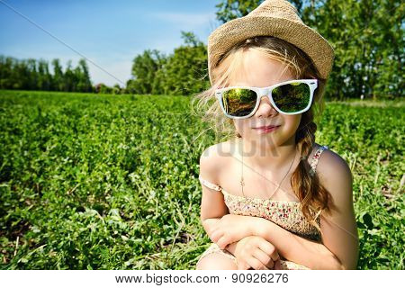 Cute little girl on a meadow in summer day. Happy childhood.