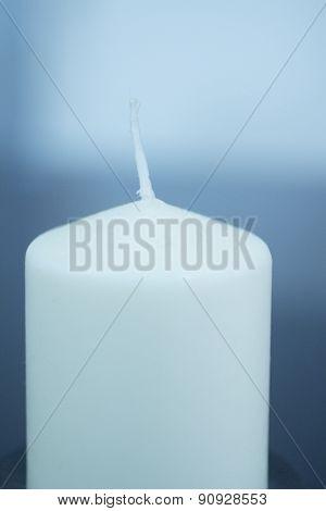 White Candle On Plain Blue Studio Background