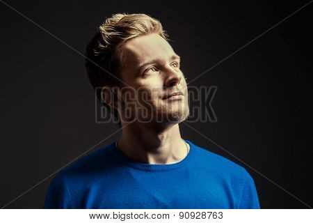 Close-up portrait of a handsome young man dreamily looking up. Men's beauty, fashion.