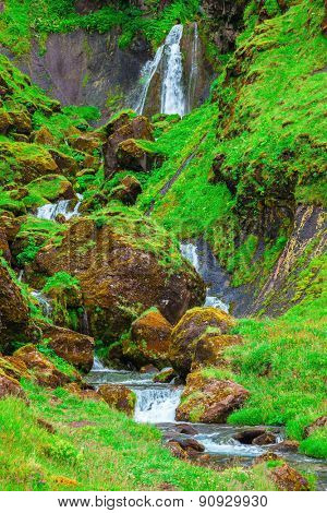July in Iceland. Picturesque cascade multi-stage waterfall. Mountains covered with green grass and moss