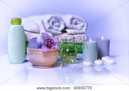 spa items with lilac orchid on blue background