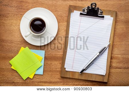 desktop concept - clippboard with blank paper and pen, sticky notes and coffee