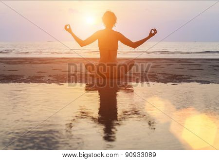 Silhouette young woman practicing yoga on Ocean beach at surrealistic sunset.
