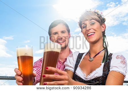 Couple on mountain hut in the Alps drinking wheat beer