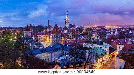 Panorama of aerial view of Tallinn Medieval Old Town with St. Olafâ??s Church and Tallinn City Wall illuminated in twilight, Estonia