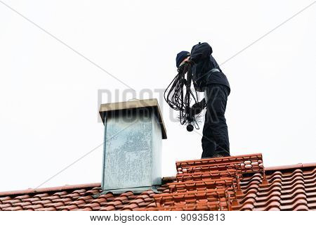 Chimney sweep standing on roof of home working