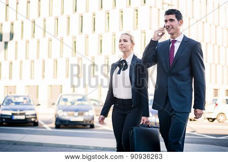 Business people in front of office building wearing briefcase and talking to smart phone