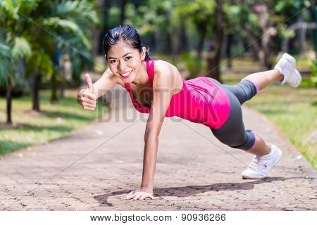 Proud and successful woman doing sport push-up in tropical Asian park, giving the thumbs up sign during her exercise