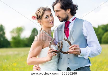 Wedding couple showing horse shoe