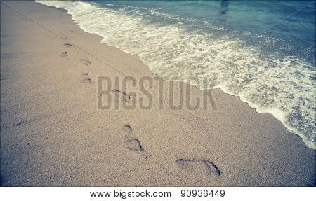 Footsteps in the sand at the beach - retro styled photo