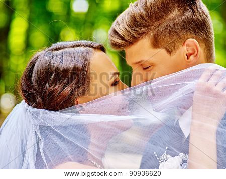 Bride and groom hiding behind veil kissing summer  outdoor.