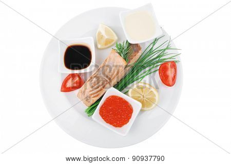 savory fish portion : norwegian salmon fillet pieces roasted with chinese onion, lemon, rosemary twig and red caviar on white dish isolated over white background