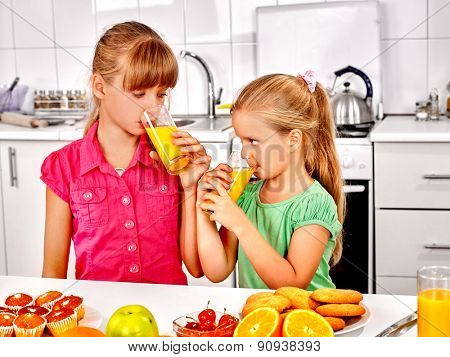 Happy children   breakfast at kitchen and drink orange juice.