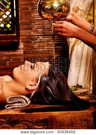 Young woman having oil Ayurveda spa treatment. Massage oil poured on forehead.