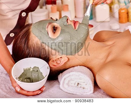Woman with green clay facial mask in beauty spa.