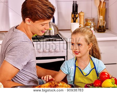 Young man cooking chicken with daugther at kitchen.