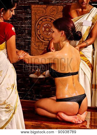 Young woman having oil Ayurveda spa treatment. Gurl sitting on her lap.