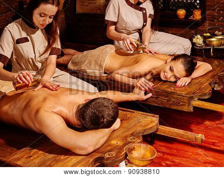 Couple  having stone Ayurveda spa treatment. Looking at each other.