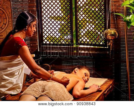 Young woman having oil Ayurveda spa treatment. Window background.