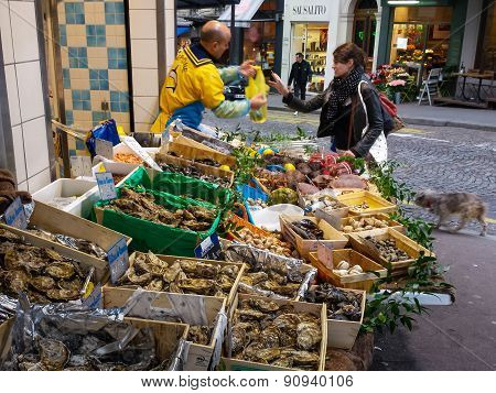 Woman shops for oysters at an outdoor market in Paris