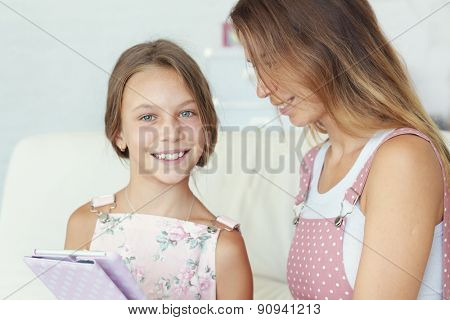 Mother with her preteen daugher playing ipad together