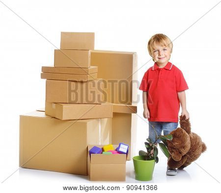 Happy child with unpacking cardboard boxes over white background.