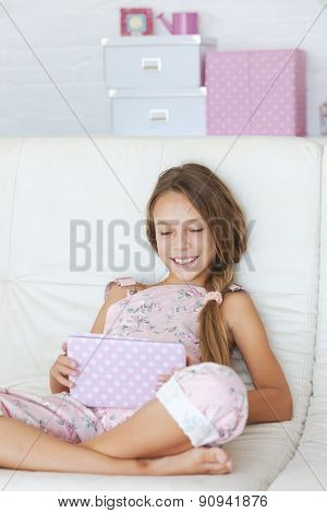 Preteen school girl of 8-9 years old playing on ipad tablet pc on a sofa at home