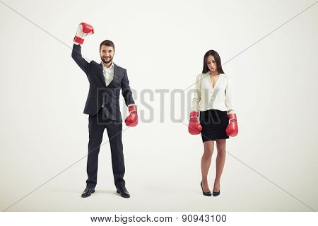 businesswoman loser and smiley winner businessman in red boxing gloves isolated on white background