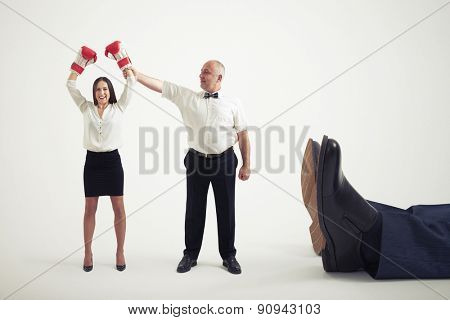 smiley referee holding winner businesswoman in boxer gloves and looking at her, near lying big legs of knocked out businessman. isolated on light grey background