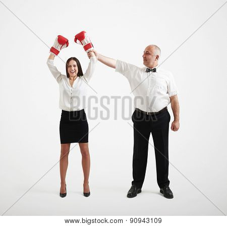 smiley referee holding happy winner businesswoman in boxer gloves and looking at her, isolated on light grey background