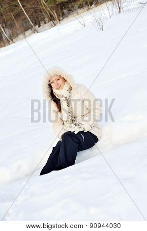 Young  Woman Sitting At Snowbank