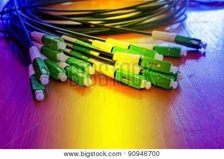 A group head connector fiber optic green color on brown table made with pastel color.Fiber Optics co