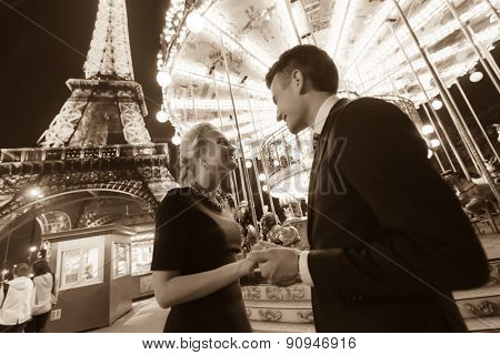 PARIS - SEP 08: couple near Eiffel tower at night on September 08, 2014 in Paris, France. The Eiffel tower is the most visited monument of France.