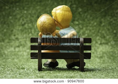 Back doll couple sitting on chairs on the lawn made vintage color.