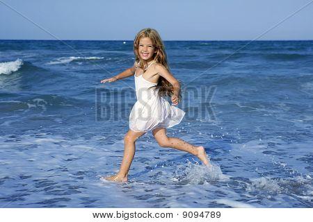 Little Girl Running Beach In Blue Sea