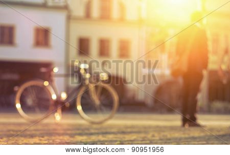 Blurred man with bicicle stay on the street at sunny day.