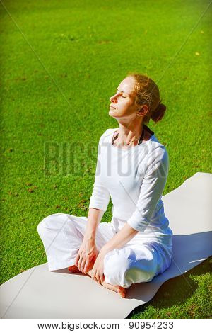 Young woman practices yoga outdoor