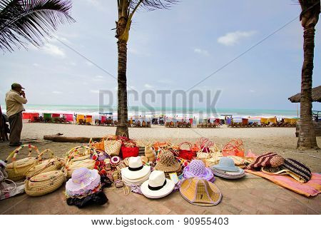 Street vendor selling straw hats and handbags, Pedernales beach, popular vacation spot in Ecuador.
