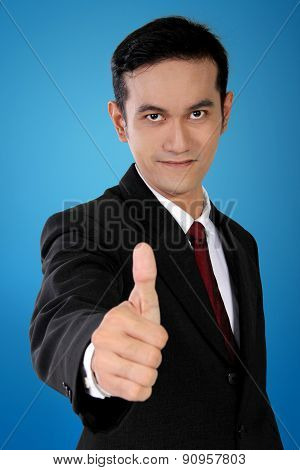 Young Asian Businessman With Thumb Up Gesture, On Blue Background