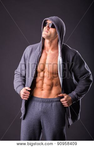 Young muscular man with open jacket revealing muscular chest and abs