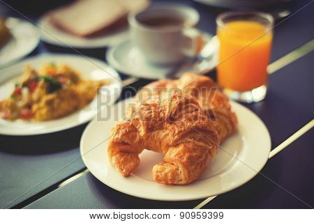 Croissant Breakfast Served With Black Coffee And Breakfast Menu.