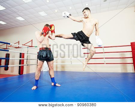 muai thai sportsman fighting at training boxing ring