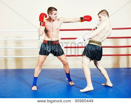 muai thai sportsman fighting at training boxing ring