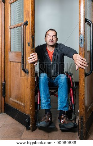 Man in wheelchair stuck between swing doors