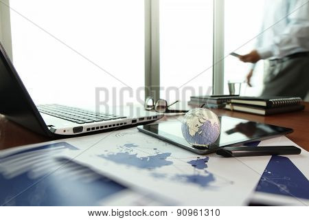 Business Documents On Office Table With Texture The World On Digital Tablet And Man Using Smart Phon