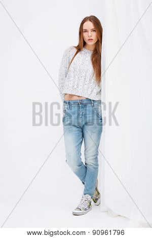 Portrait Of Young Woman Standing Against Curtains.