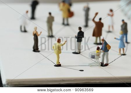 Close Up Of Miniature People With Social Network Diagram On Open Notebook On Wooden Desk As Social M
