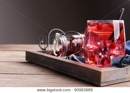 Compote with red currant on tray on wooden table, on dark background